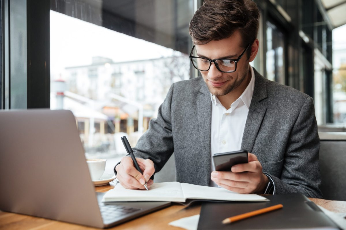 smiling businessman eyeglasses sitting by table cafe with laptop computer while using smartphone writing something scaled