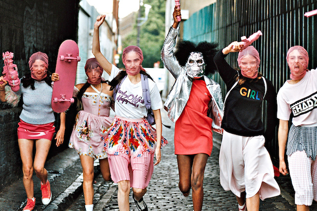 A young girl gang marching down an alley, in feminne clothing and sheer pink face coverings, hold up pink plastic weaponry and skateboards in defiance