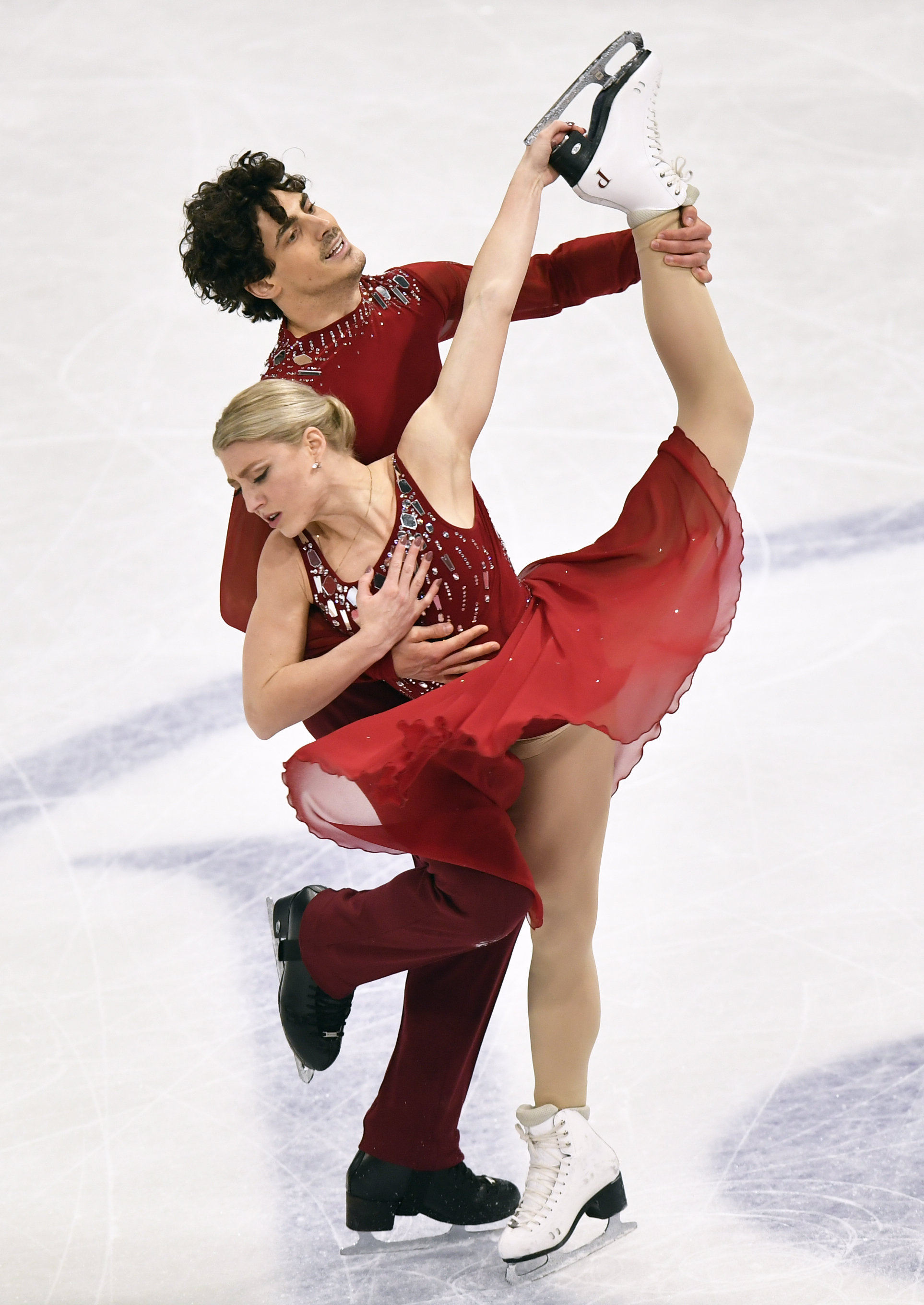 Two ice dancers perform a spin