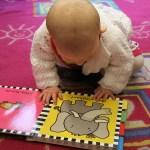 Enfant à la crèche regardant un livre en anglais