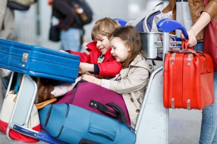 Enfants sur un chariot de bagages