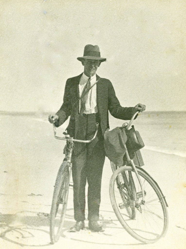 Norman holds bikes for photo at beach, c.1919.