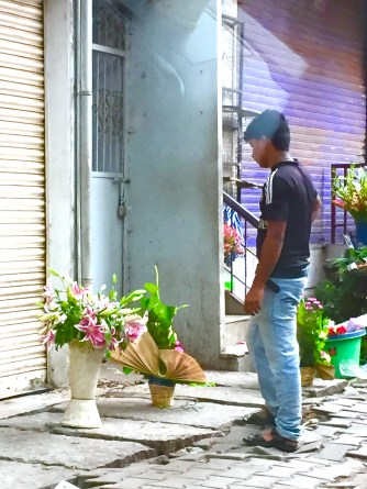 A man admires his roadside flower arrangement.