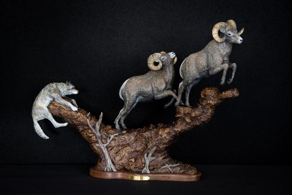 A clumsy wolf chases two rams in the bronze 'Leap of Faith' (viewed from front)