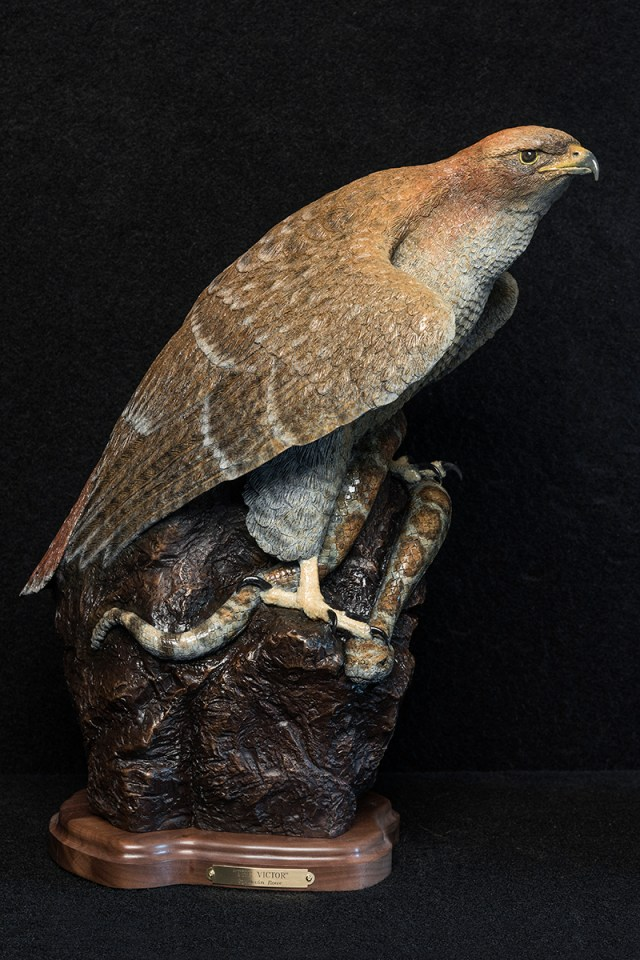 A hawk stands victorious over a snake in the bronze 'The Victor' by Devon Rowe.