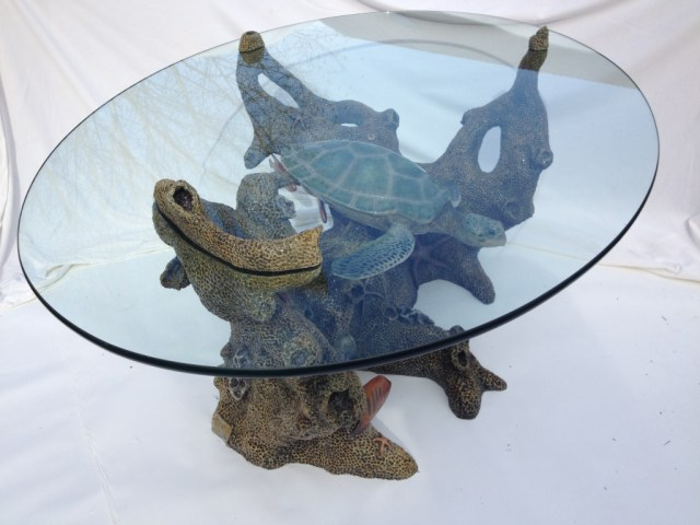 """A glass top table with a turtle and fish swimming amidst coral below in the bronze """"Turtle Table"""". (full view)"""