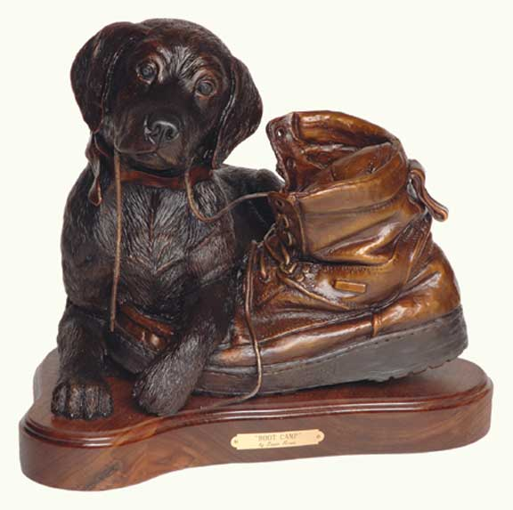 The bronze 'Boot Camp' depicts labrador puppy straddling the front of a boot with shoelace in mouth.