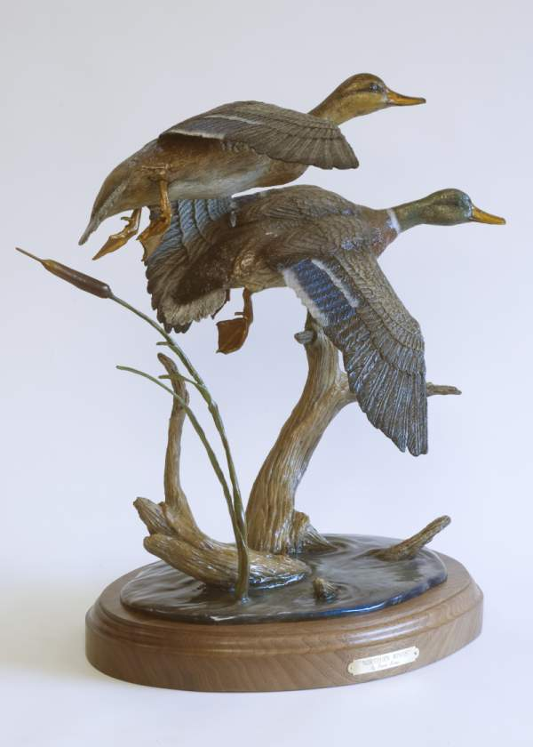 Ducks fly above cattails in the bronze 'Northern Winds' by Devin Rowe.