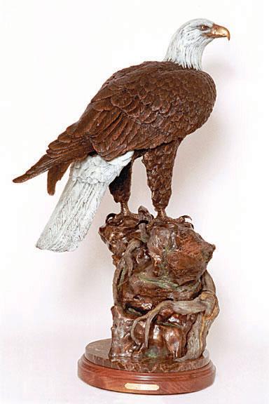 A bald eagle perches in the bronze sculpture 'Quest'.