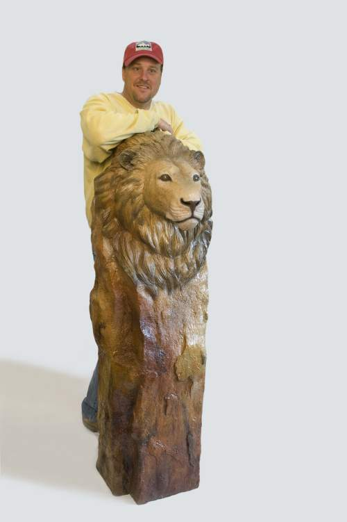 The bronze sculpture 'Serengeti Sunset' of a lion bust with artist Devin Rowe.
