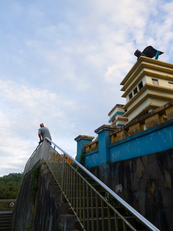Resting area and view point at Tomohon (Sulawesi, Indonesia): Yoeri on steps and evil owl with red eyes on tower