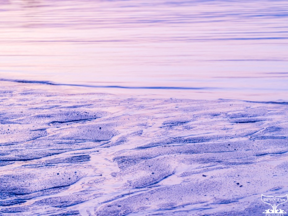 Art by nature of Devocean Picures: Ripples in the sand forming little landscapes, above the sea with motion blur due to long exposure (blue, purple and light orange and yellow dominate the picture)