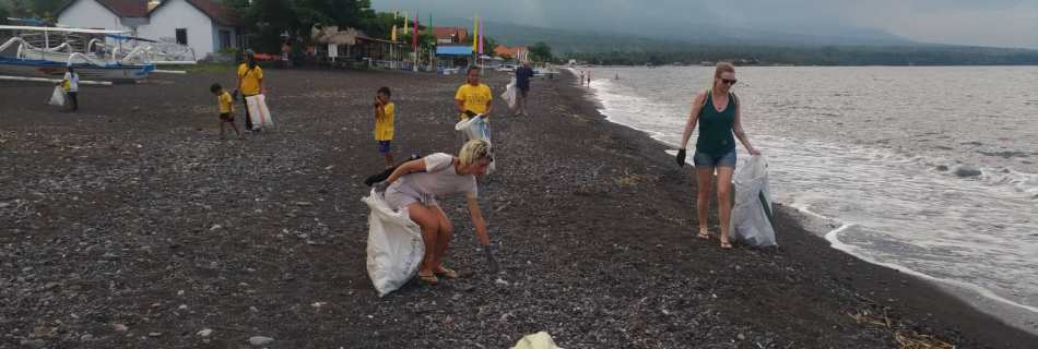 The group of volunteers of Trash Hero Amed spreads out along the beach to clean up plastic Nicki with rice bag in hand on the right side. IN the back houses, trees, the sea and a clouded sky.