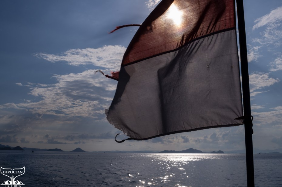 Indonesien flag at the back of a boat, ocean, sun and clouds.