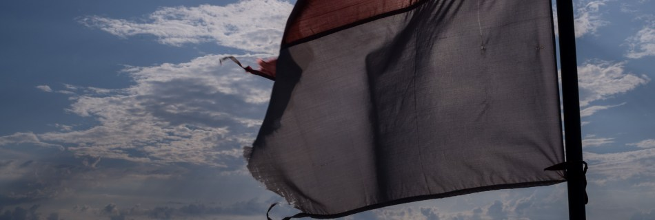 Indonesien flag at theback of a boat, ocean, sun and clouds.