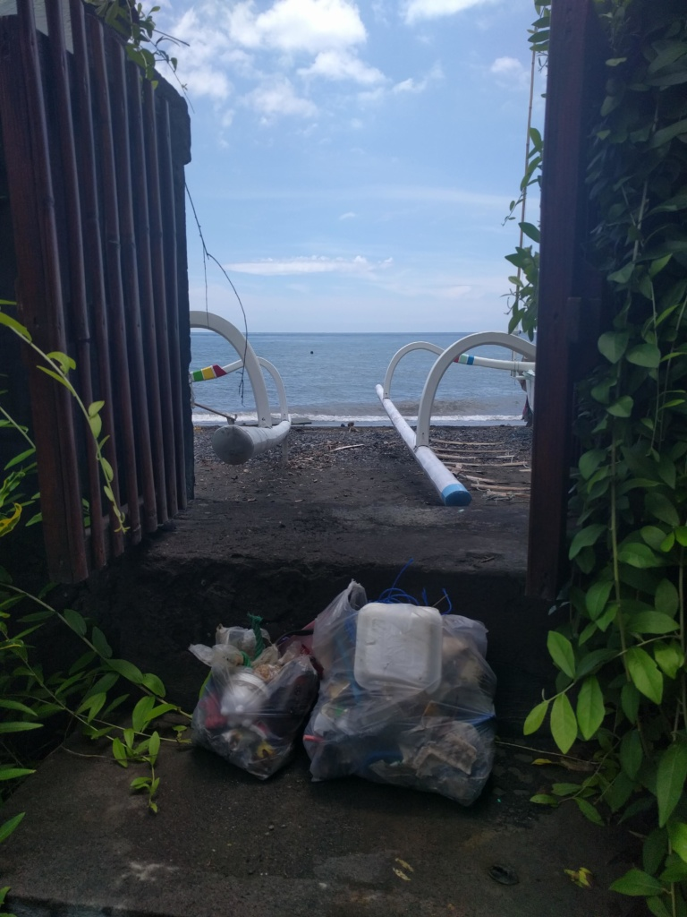 Two bags standing on our doorstep filled with rubbish collected at the beach which can be partly seen through the open gate. Beach with two boats, blue sea, blue sky with some clouds.
