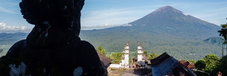 "View from the stairs of temple ""Pura Lempuyang"" in East Bali, Indonesia, showing the court with selfie opportunities in the Heaven's Gate and view to mount Agung. On the left side is a stone statue looking into the picture."