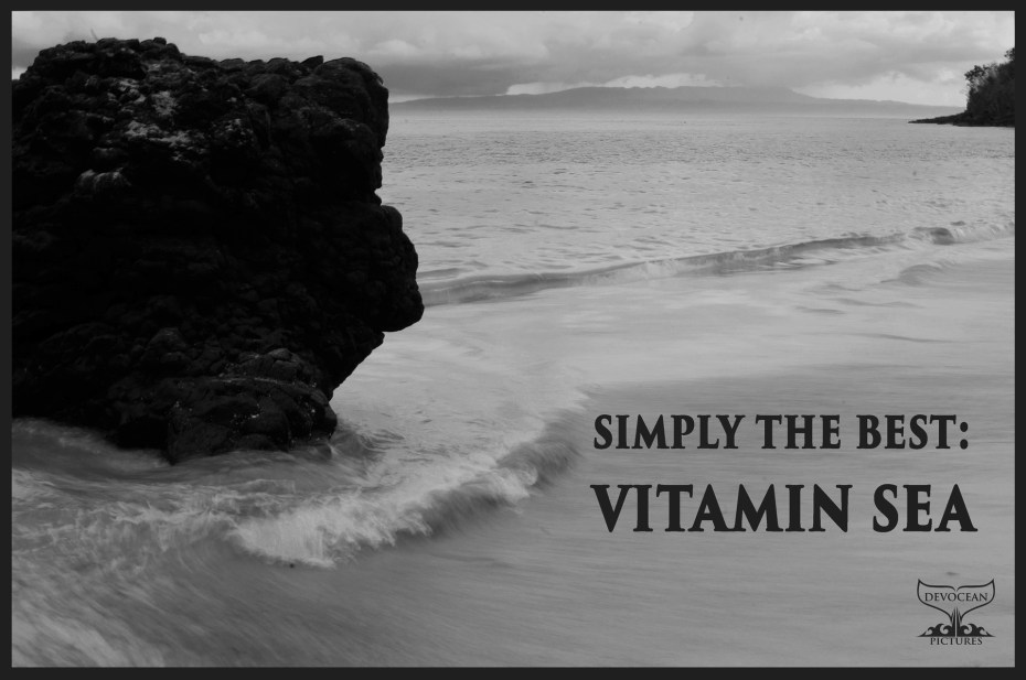 """Black and white picture of the sea at the East coast of Bali: White Beach with a rock on the left and small incoming waves in long exposure / slow shutter speed. Postcard with warm regards with text: """"Simply the best: Vitamin Sea"""""""