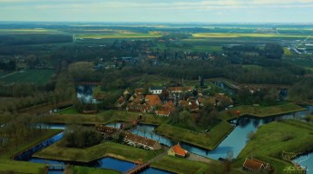 """Screenshot of video clip """"Take a Minute to fly 03: Fort Bourtange"""" an aerial shot showing the intriguing patttern of the fortress build in the Dutch swamps with a 6-pointed star shaped of water ways (Canals) around plus additional lakes and lines of defence in the Northern part of the Netherlands."""