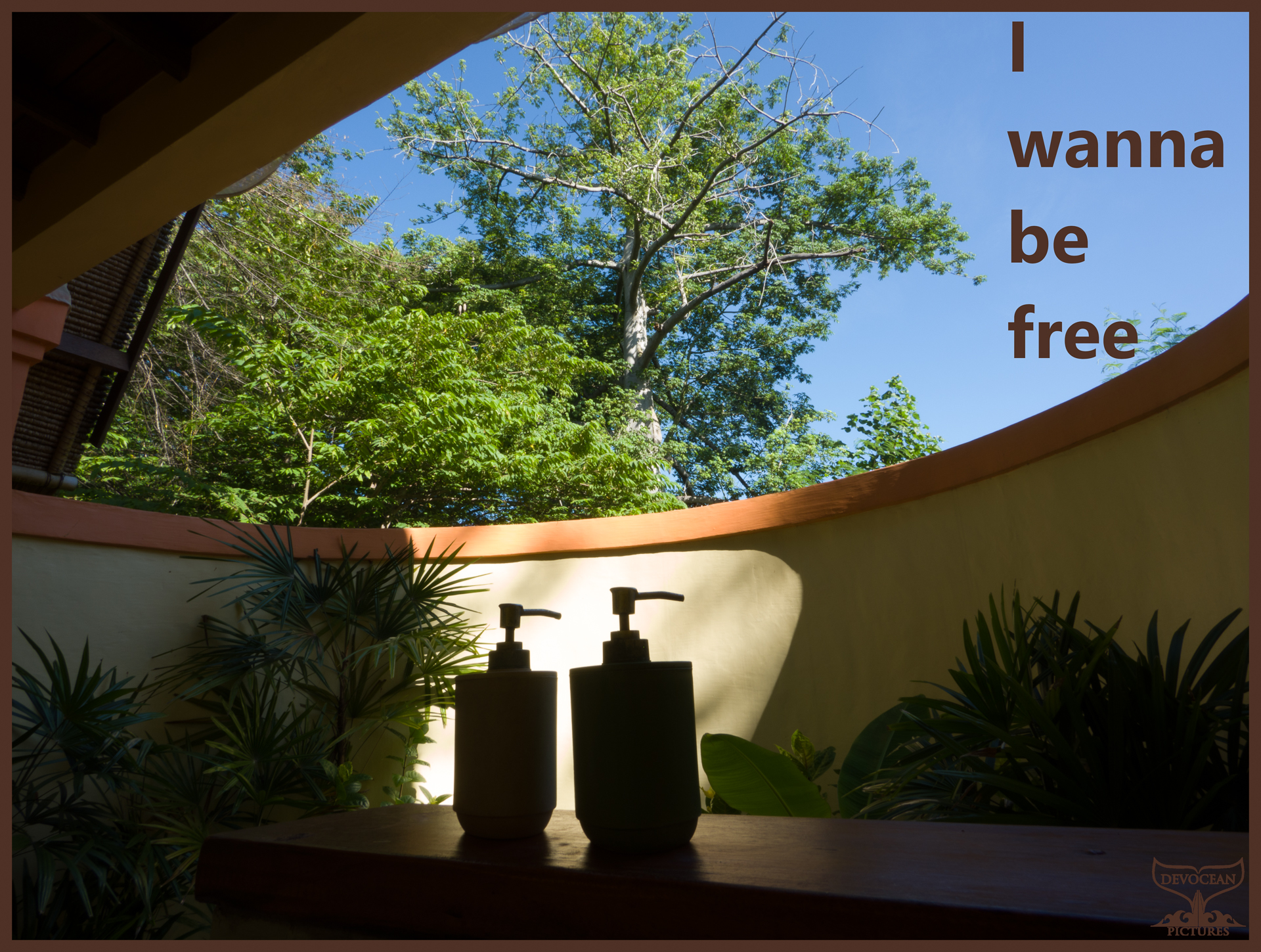 View over a yellow wall of an outside bathroom in Pemuteran, Bali, to the trees and the blue sky.