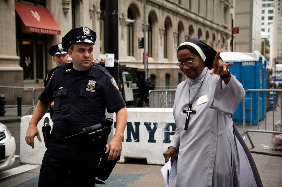 A cop assists a nun in the street