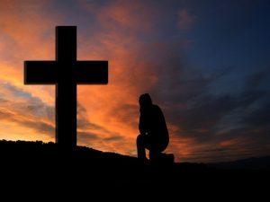 man at cross praying