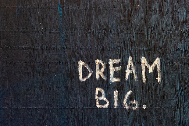 """Black textured background with white letters painted one that say """"Dream Big"""""""