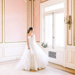 bride standing by a window in wedding gown