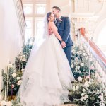 bride and groom kissing on a staircase decorated with wedding flowers -Cairnwood Estate Wedding Shoot