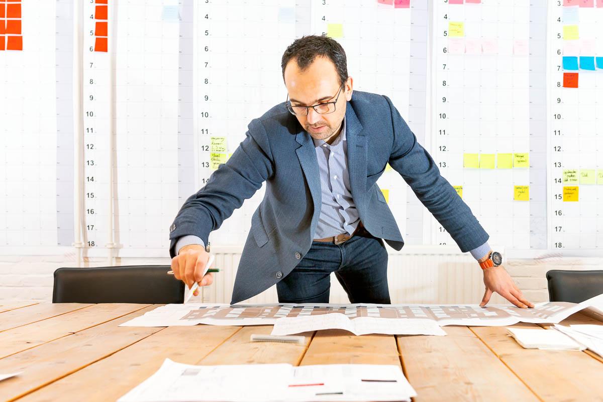 Portret van een projectmanager in de bouw, gebogen over een tafel met een projectplanning voor APG Bouwpensioen magazine