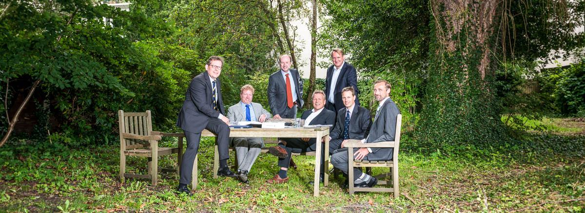 Fiscaal juristen portretrond een tafel in een weelderige tuin