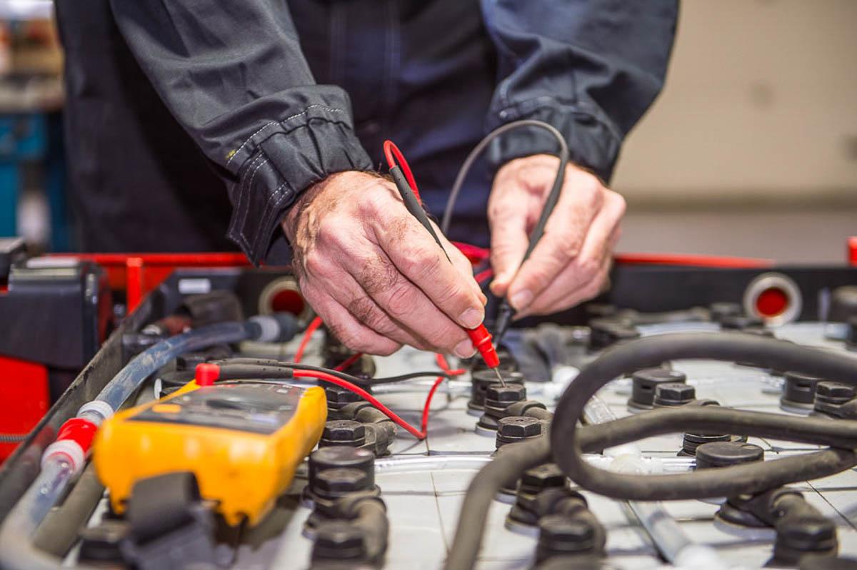 Monteur controleert de spanning van een vorkheftruck batterij