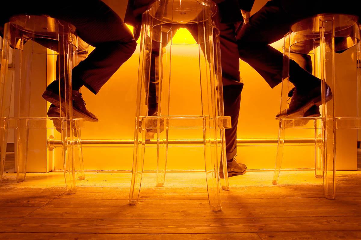Drie mannen in pak op perspex barkrukken aan de bar tijdens de VrijMiBo