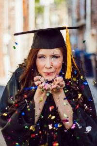Graduate woman blowing confetti