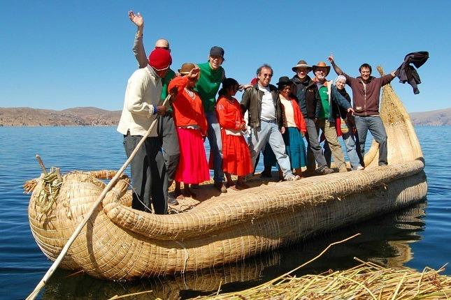 Eine viventura Reisegruppe stehen mit Einheimischen in einem Schilfboot am Titicacasee.
