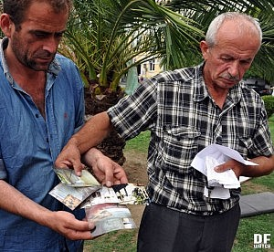 Alexandre Iremadze shows photos of his old house, which was damaged by the landslide (DFWatch Photo)
