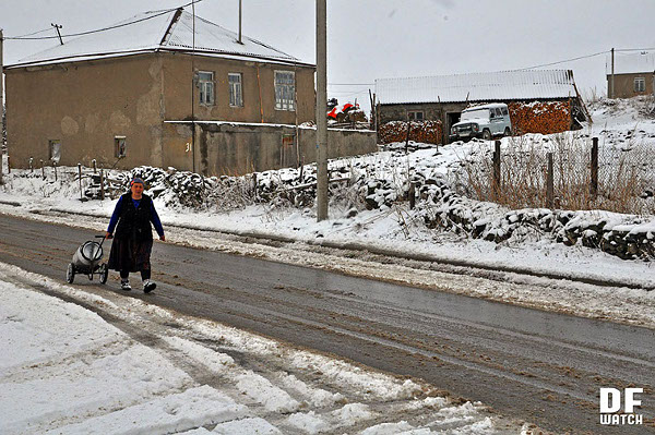 Woman pulling a milk contained along snowy road
