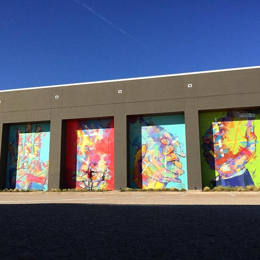 Four of Adrian Torres' large murals at Legacy Central with a man jumping in front for scale