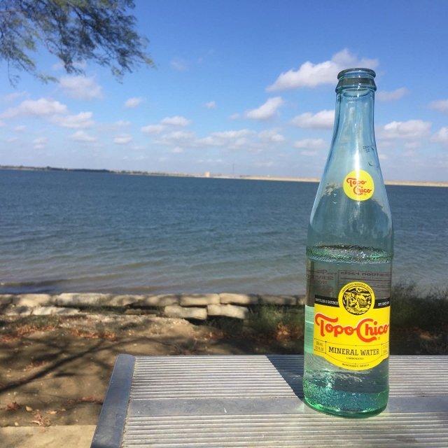 Joe Pool Lake at Cedar Hill State Park with a bottle of Topo Chico in the foreground.