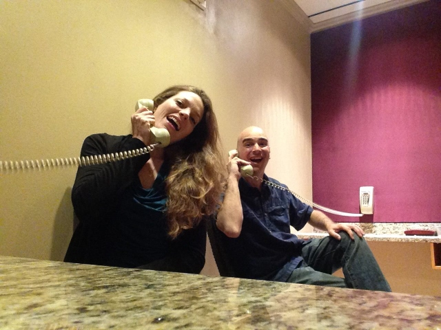 A woman and man smiling and answering a telephone to convey the idea of positive customer service.
