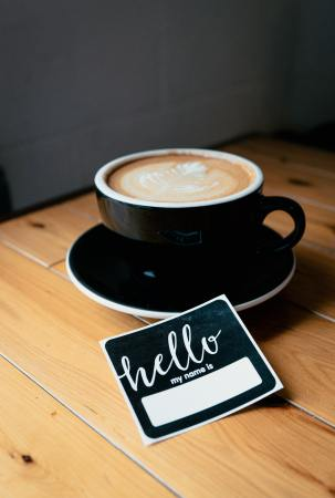 latte coffee in a mug on a coffee plate next to a name tag that says