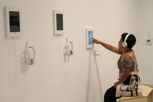 Person with headphones using a touch screen in a white gallery space