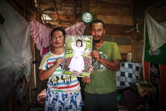 Sumitra (38) a scavenger and wife of Iin (35) holds a beautiful photo (5) of their child who died from cough and shortness of breath. Dharma Wijayanto