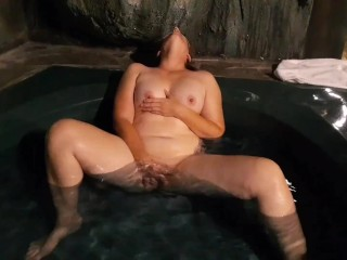 Nymph plays with herself in her secret grotto hot tub