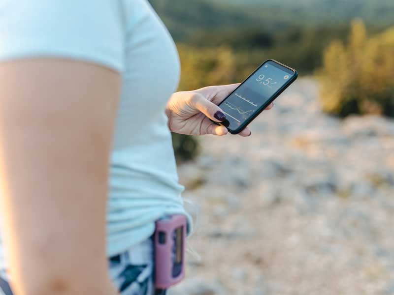 Woman with diabetes wearing an insulin pump and checking her blood glucose on a smart phone app
