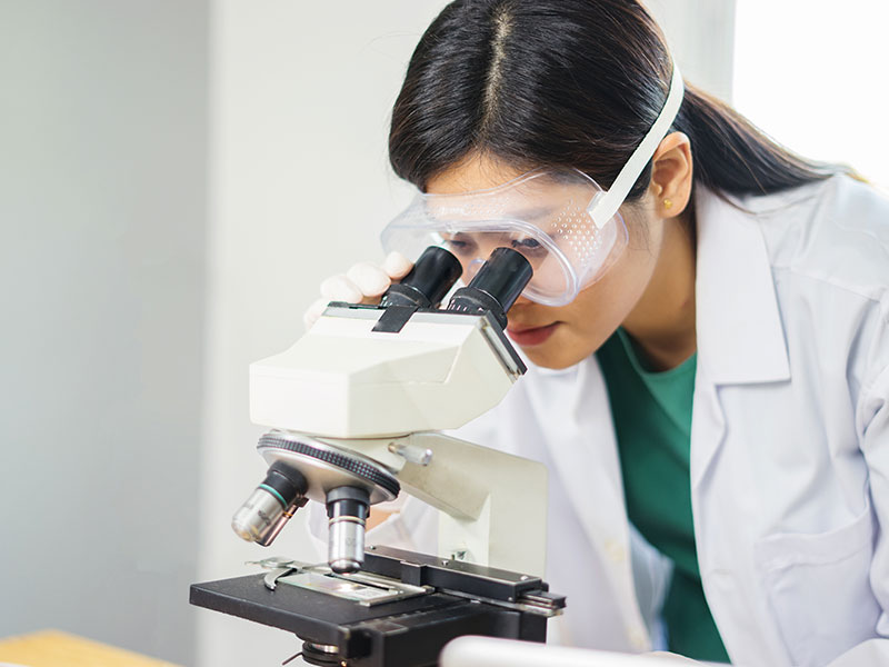 Research scientist looking through a microscope in a laboratory