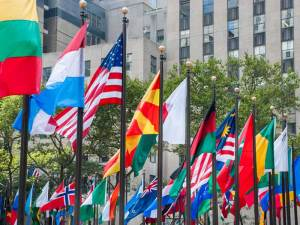 Rows of flags of all nations next to UN in New York