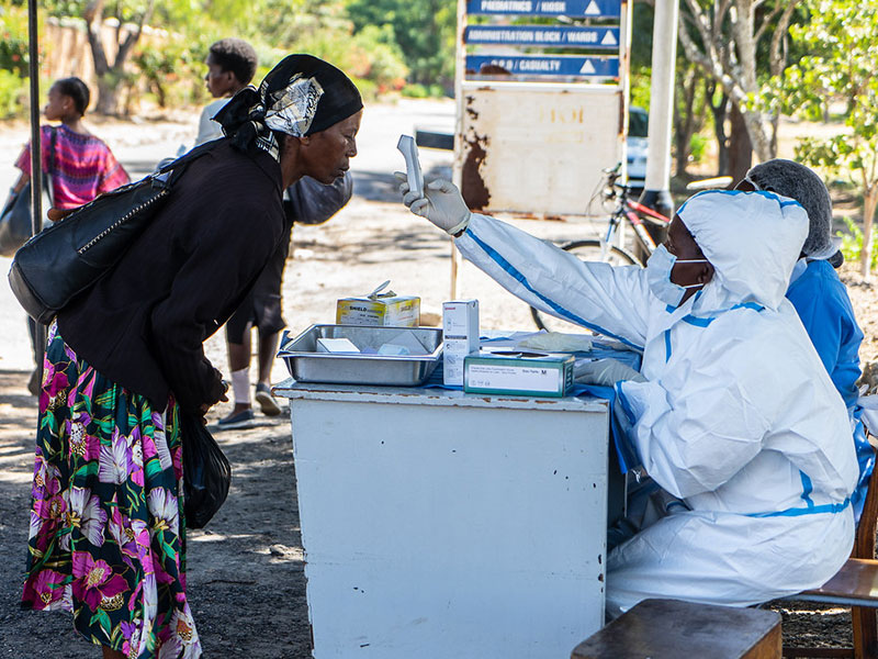 A woman gets her temperature checked before entering Mpilo Hospital.