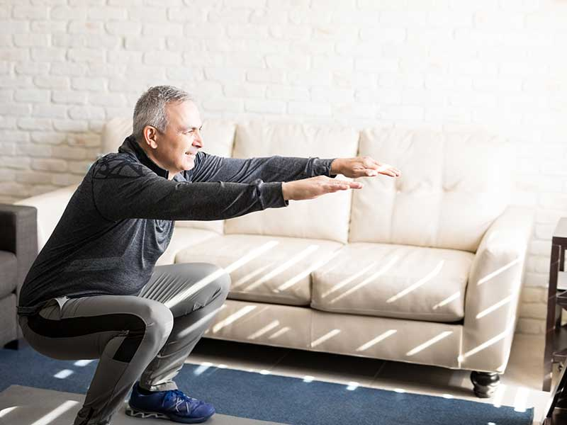 Mature man doing squats at home