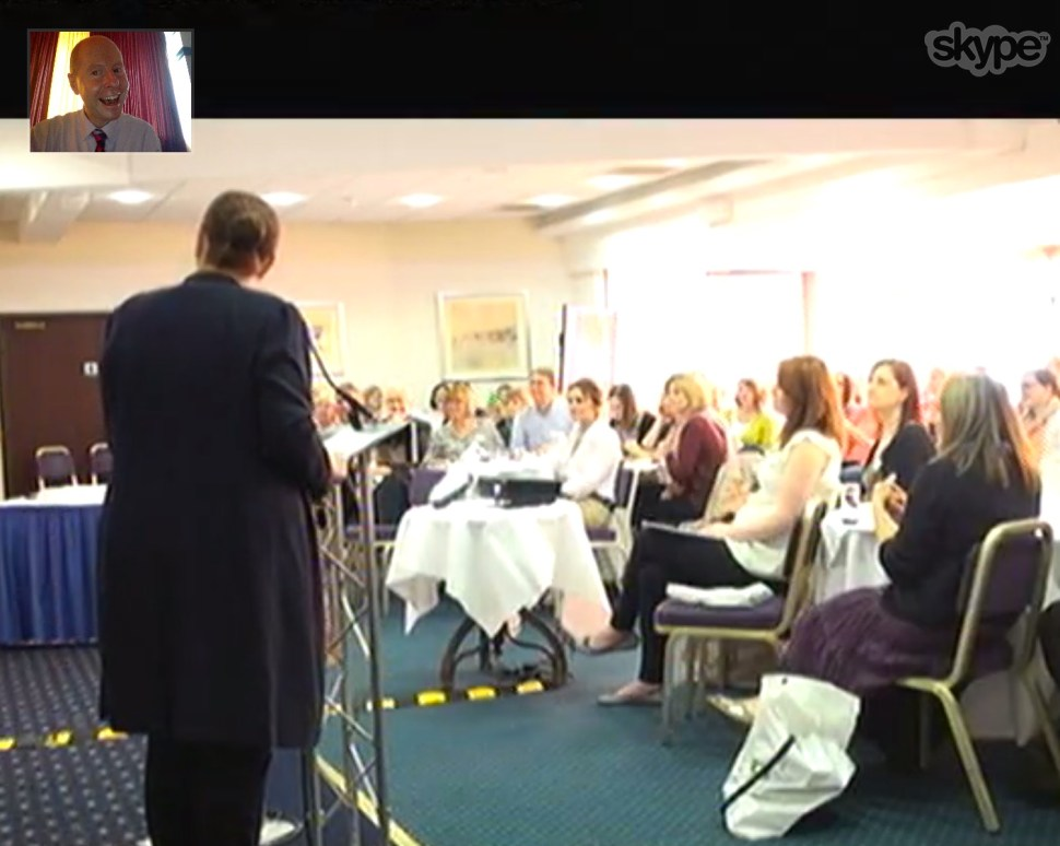 Armstrong (upper left screen) lecturing by video to the Scottish Symposium with Sandra Jones, chairperson, at the podium